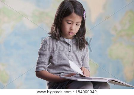 Korean girl reading book near map