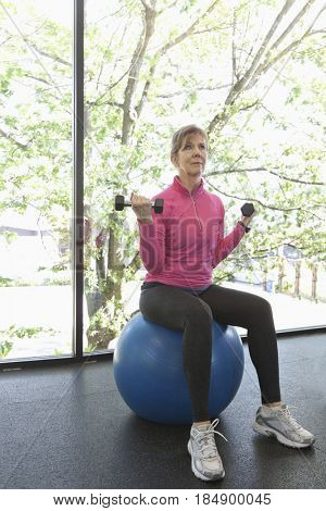 Woman sitting on exercise ball lifting weights