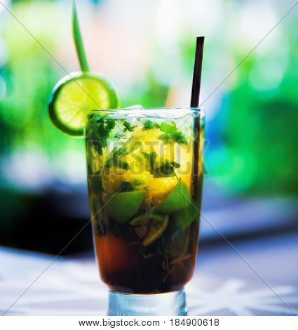 Colorful mojito coctail with blurred green background behind