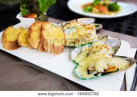 Plate with baked mussels with cheese and toasts