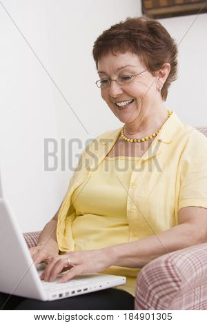 Senior Chilean woman typing on laptop