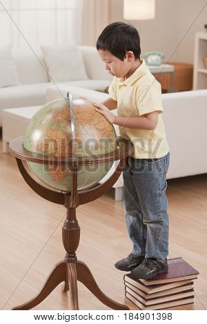 Korean boy looking at globe