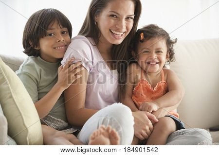 Girl sitting on sofa with brother and sister