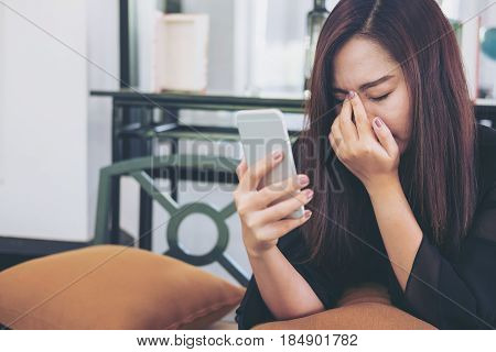 A beautiful asian woman looking at smart phone with feeling sad and cry in cafe
