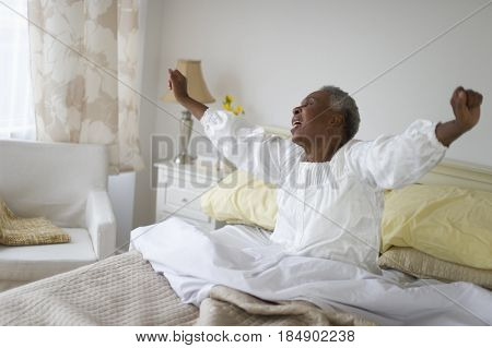 Black woman waking up in bed