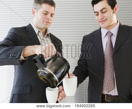 Businessman pouring coffee for co-worker