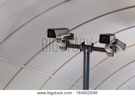 Security camera on the blue wall in summer day