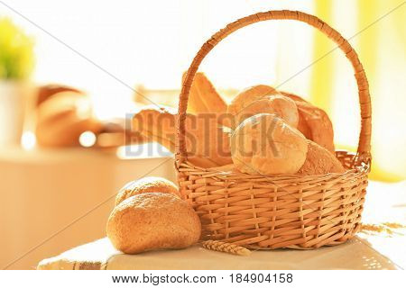 Wicker basket with different types of fresh bread on table
