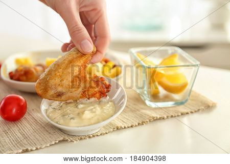 Hand of woman eating chicken wings with tasty mayonnaise sauce, closeup