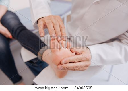 Testing reflexes. Delicate dedicated wonderful expert trying not hurting his patient while conducting a checkup on the joints functioning