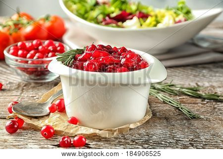 Delicious cranberry sauce in bowl on wooden background, close up