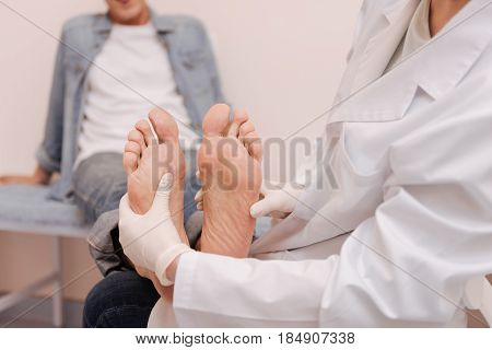 Consultation look. Prominent busy local doctor using special gloves for examining mans feet and figuring out the diagnosis