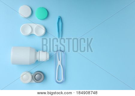 Cases for contact lenses, tweezers and bottle of solution on blue background