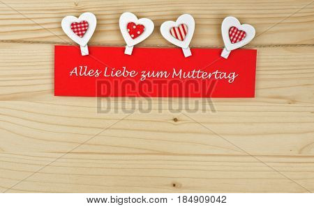 Four hearts with clothes pegs and red paper and the german words for all love on mother´s day on a cord on wood