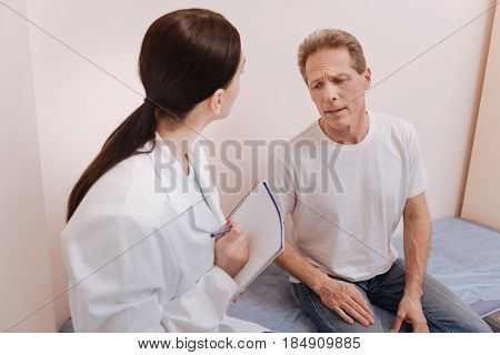 Pain is unbearable. Concerned hurt middle aged patient visiting his doctor and explaining what he feeling while having some troubles with his back