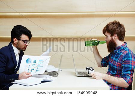Different attitudes to work: hard-working bearded employee in formalwear analyzing financial documents while his lazy coworker playing computer games and drinking beer, profile view