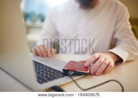 Close-up shot of unrecognizable businessman in buttoned-up white shirt sitting at cafe table and using laptop connected to external hard drive
