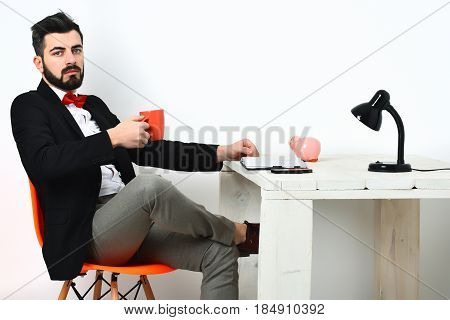 Bearded man short beard. Caucasian serious hipster with moustache holding orange mug at white wooden table wearing black jacket white shirt and red bow tie isolated on white background
