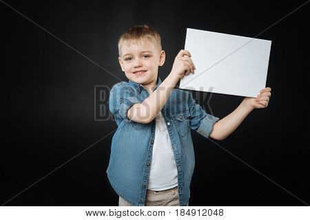 Just look at me. Positive delighted boy wearing casual clothes rising his arms while looking straight at camera