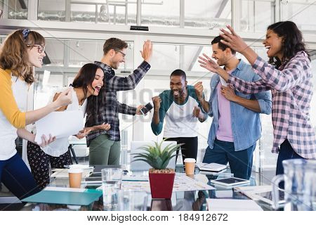 Cheerful creative business team standing around table at office