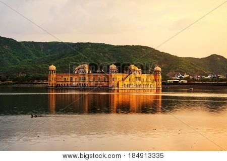 Jaipur, India. Jal Mahal palace at sunset in Jaipur, India. Popular landmark surrounded by water. Mountains at the background