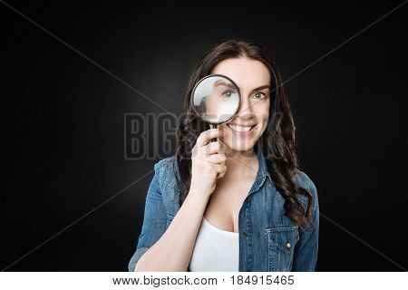 I watch you. Young cute smiling brunette looking forward holding her right arm bent in elbow while standing over black background