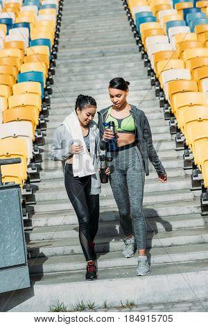 Smiling young sportswomen with sports bottles walking between stadium seats