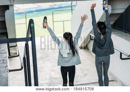 rear view of two happy sportswomen in sportswear going to the stadium