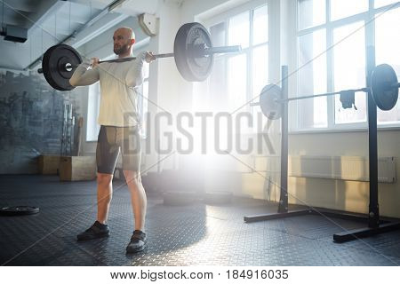 Portrait of strongman lifting heavy barbell during workout in sunlit gym, performing shoulder press