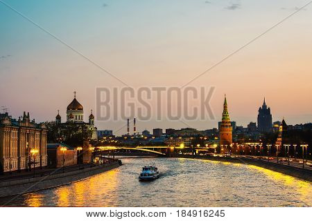 Moscow, Russia. Aerial view of popular landmark Kremlin in Moscow, Russia at night. Blurred cars at the road. Illuminated Kremlin wall, and touristic boat at Moscow river.