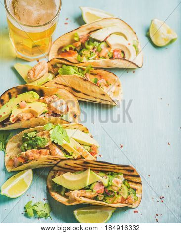 Healthy corn tortillas with grilled chicken, avocado, fresh salsa, limes and beer in glass over blue wooden background, selective focus, copy space. Gluten-free, allergy-friendly, dieting concept