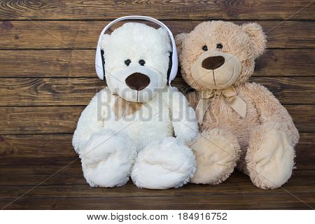 A brown teddy bear and a white teddy bear listening to music in white headphones sitting on a wooden brown background with a place for an inscription
