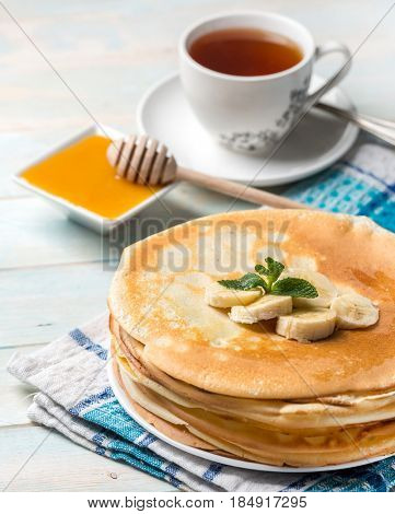 Stack of pancakes with banana topping, honey spoon and white aromatic cup of tea