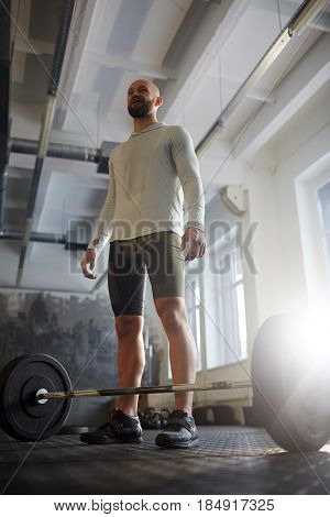 Low angle portrait of modern strongman ready to lift heavy barbell from floor  during powerlifting workout in sunlit gym