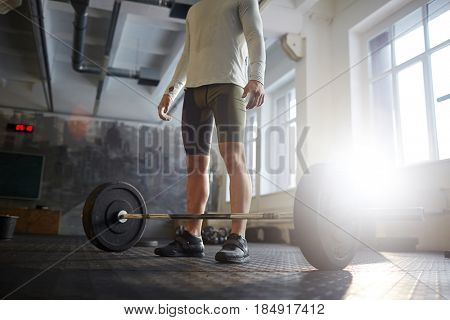 Portrait of unrecognizable strong muscular man ready to lift heavy barbell from floor  during powerlifting workout in sunlit gym