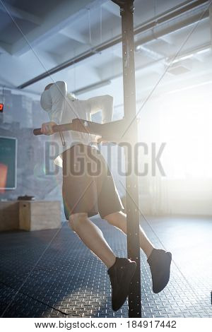 Back view of muscular man doing pull up exercises on mount rack in sunlit gym