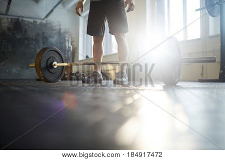 Low section of unrecognizable strong man ready to lift heavy barbell from floor during powerlifting workout in sunlit gym