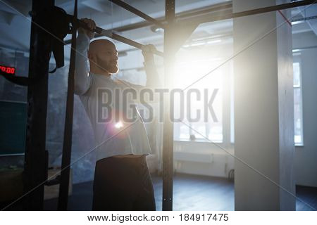 Portrait of strong bearded man performing pull ups on bar during workout in gym lit by sunlight