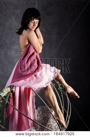 elegance girl in a pink skirt, swinging on a metal swing. holding on to chains. on a gray background