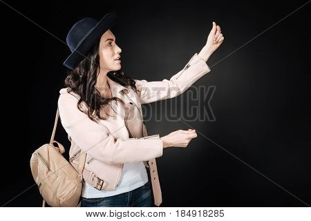 Like a tourist. Beautiful young woman with curly hair keeping backpack on the right shoulder rising both hands while looking aside