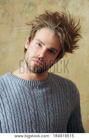guy or handsome bearded man with beard or sexy caucasian macho on beige wall background. Stylish blond hair haircut and young unshaven face skin. Male beauty and hairdressing.
