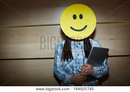 Unrecognizable black-haired businesswoman in casualwear holding modern laptop in hands while covering her face with smiling mask as sign of successful project completion, waist-up portrait