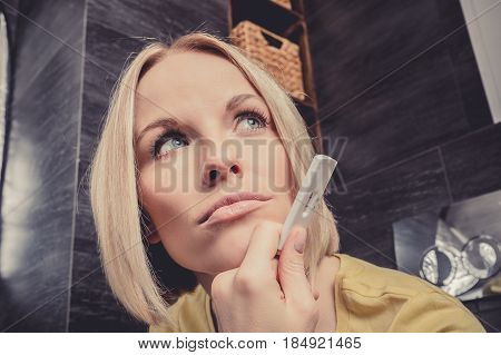 A beautiful young blonde woman sits in the bathroom and holds a positive pregnancy test. Conceptual photography.