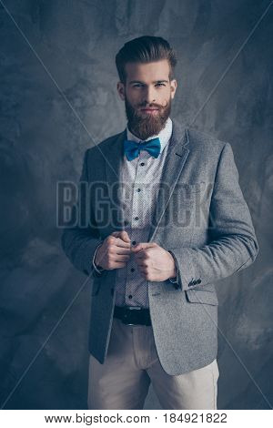 Confident stylish man with red beard and blue bow tie on gray background