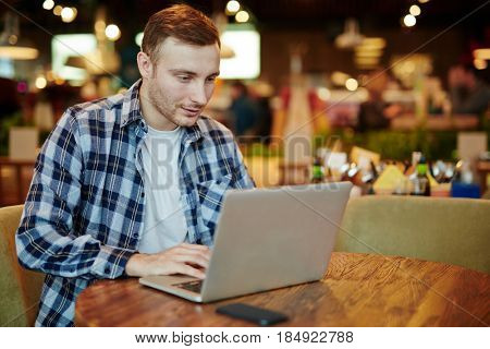 Enthusiastic young manager in casualwear creating presentation on modern laptop while sitting in cozy small coffeehouse, waist-up portrait