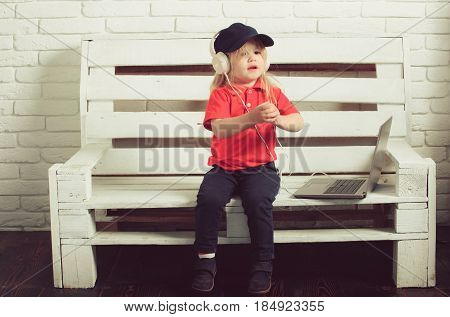 little boy or cute blonde child in headset listen music or audiobook working on laptop business and education