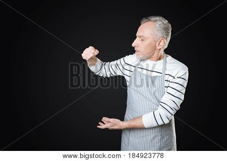 Just smell it. Gray-haired male person turning his head aside raising both hands standing over black background