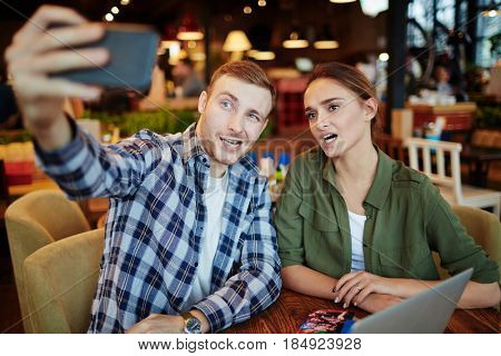 Pretty young couple having date in cozy small coffeehouse: they making faces while taking selfie on modern smartphone