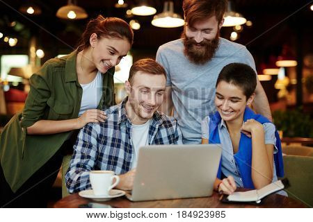 Four young friends hanging out in cozy small cafe: they enjoying delicious coffee and watching their favorite show on laptop