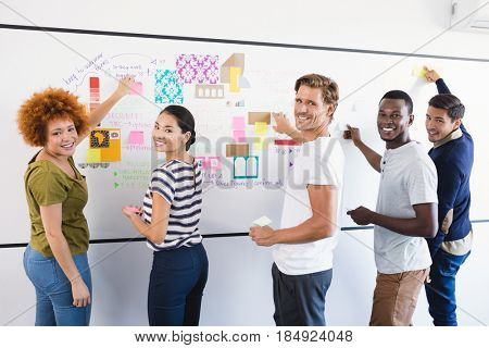 Portrait of business people sticking adhesive note during planning in office